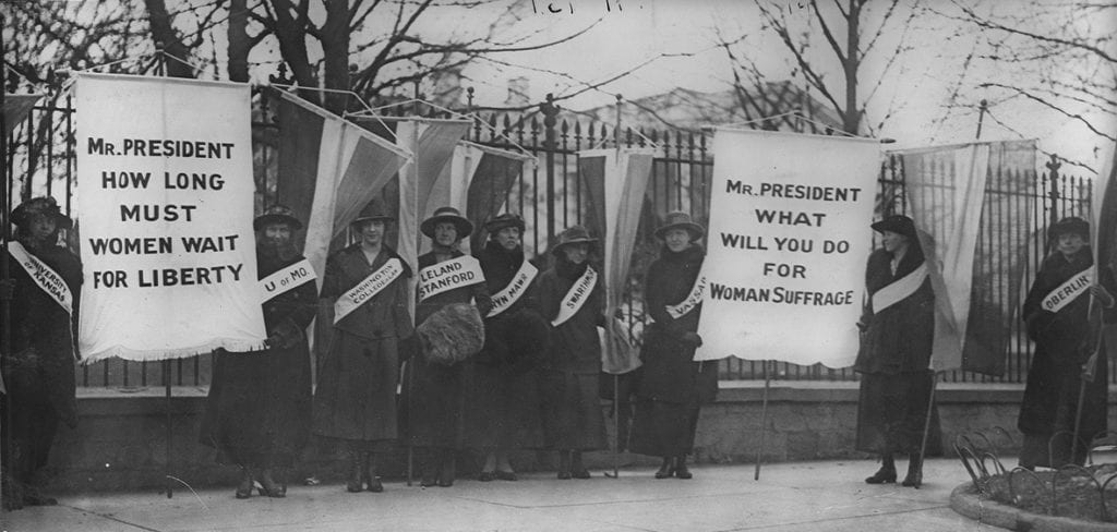 """Women picket outside the White House with signs reading """"Mr. President How Long Must Women Wait for Liberty"""" and """"Mr. President what will you do for woman suffrage"""""""