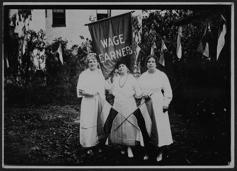 """Three women stand holding a sign that says """"wage earners"""" as well as two women's suffrage flags with womens suffrage flags behind them"""